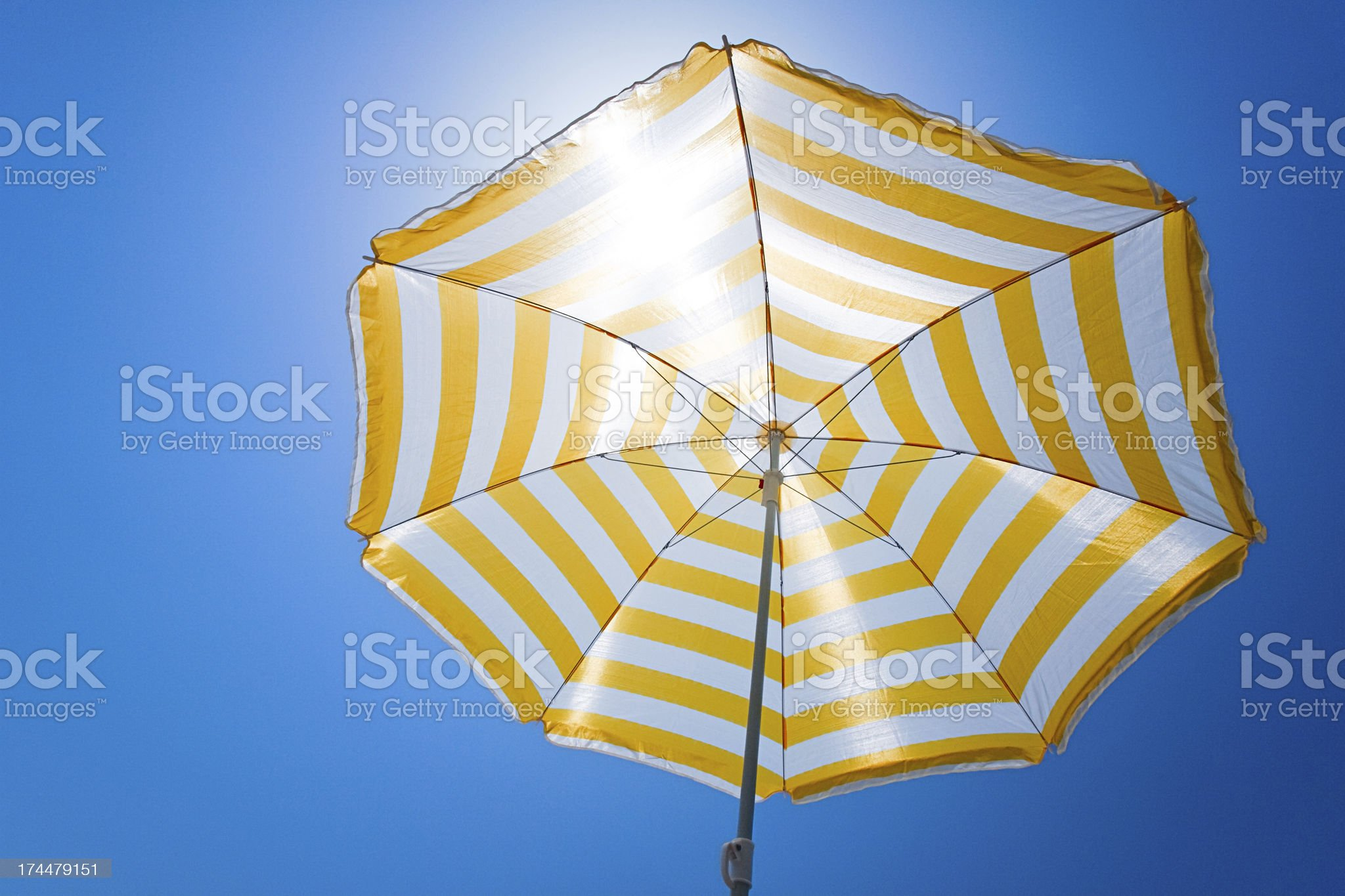Yellow umbrella against the sun and blue sky royalty-free stock photo
