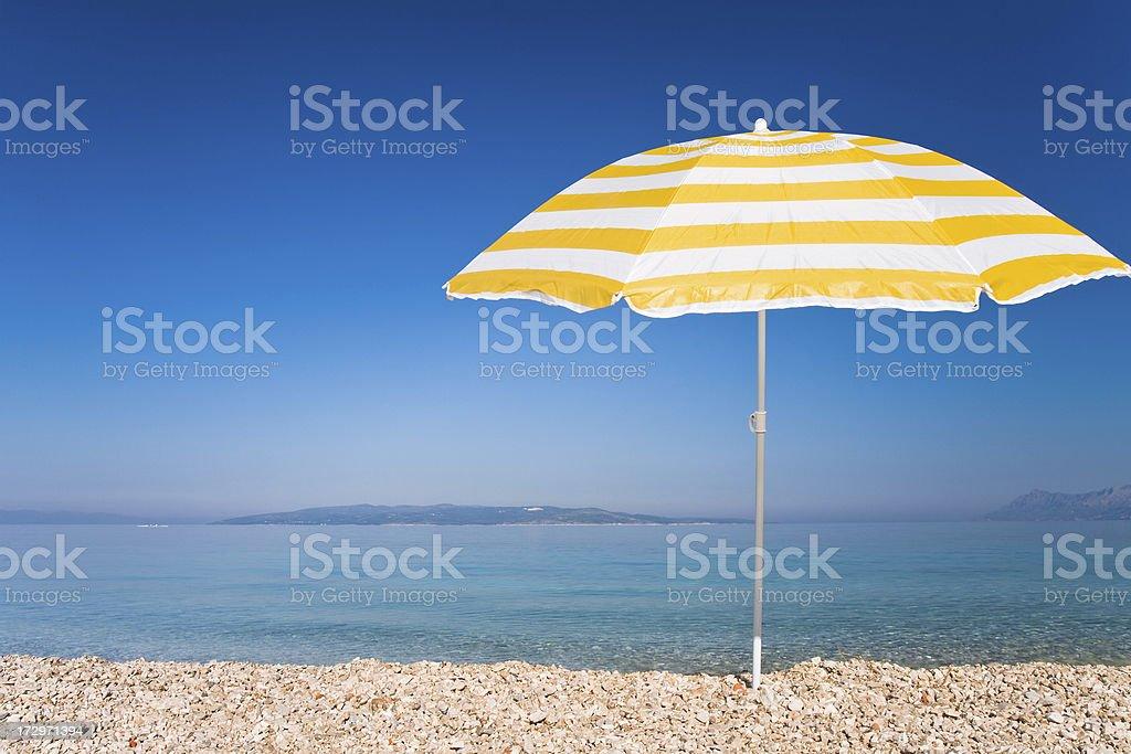 Yellow umbrella, beach, sea, the blue sky royalty-free stock photo