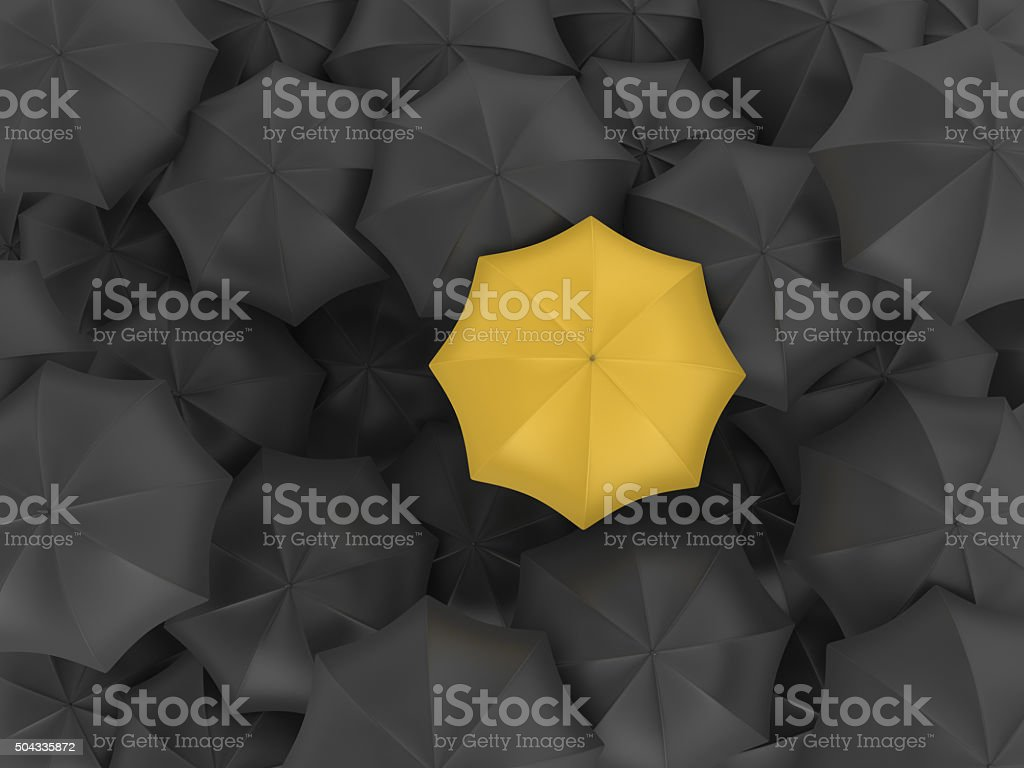 Yellow Umbrella with Many Black Ones stock photo