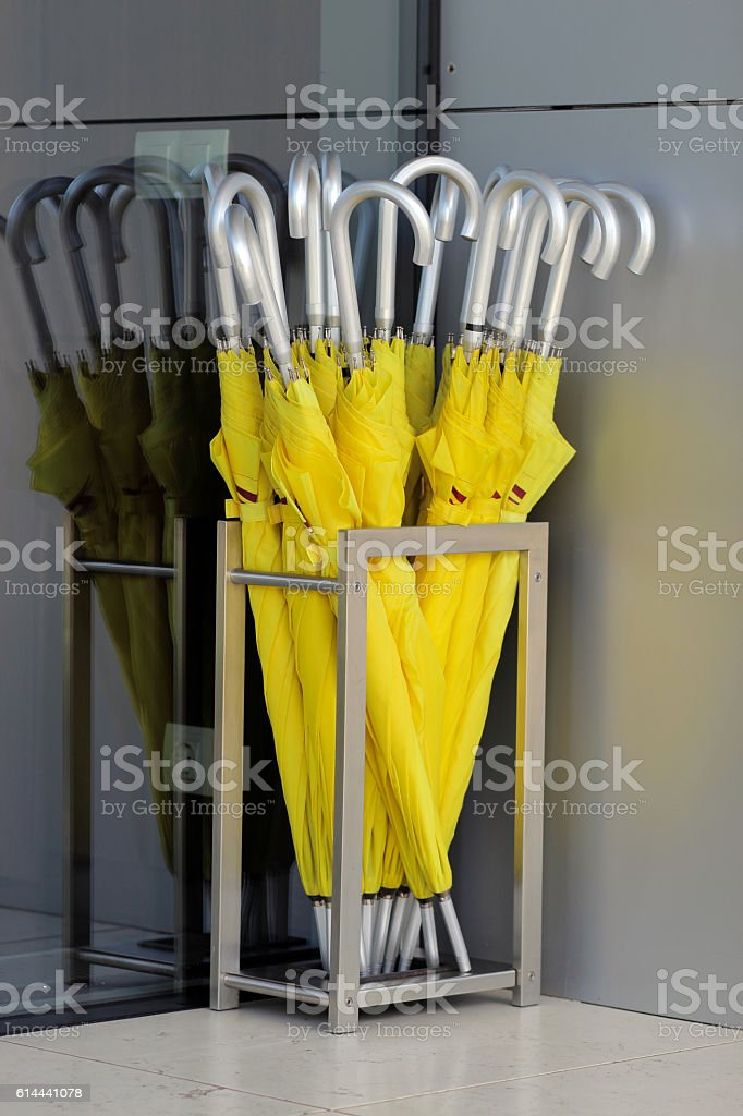 yellow umbrellas stand in a silver basket in the hotel stock photo