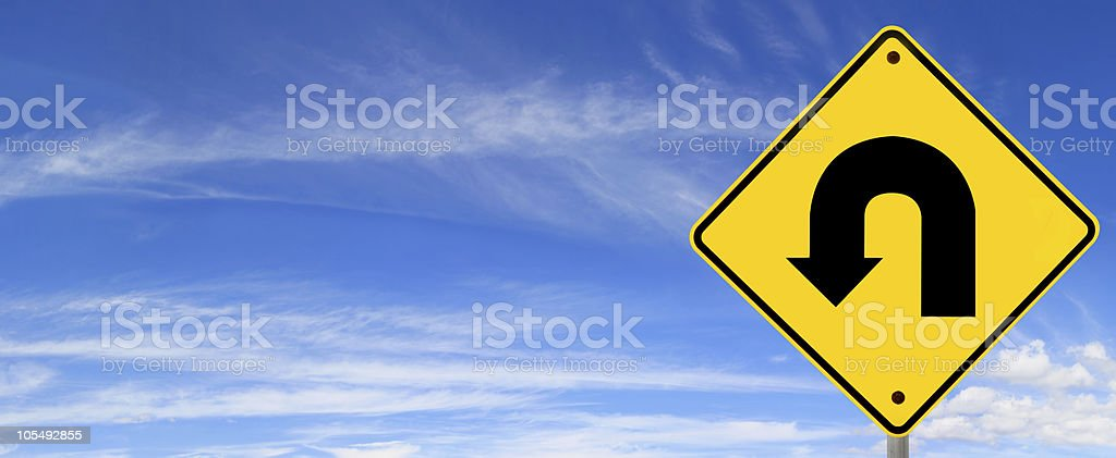A yellow u-turn sign against the sky stock photo