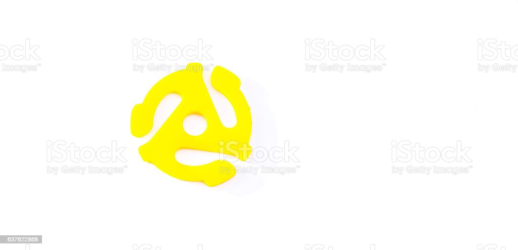 Yellow, vintage retro 45 RPM record spindle adapter on white. stock photo