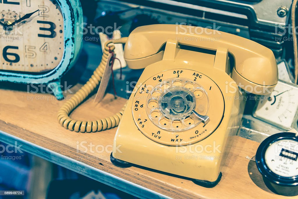 Yellow vintage Rotary Phone with toned effect stock photo