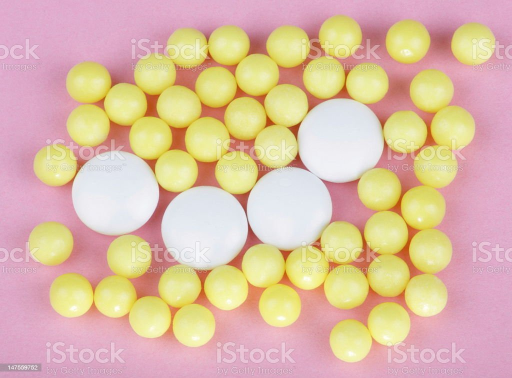 yellow vitamins on pink background royalty-free stock photo