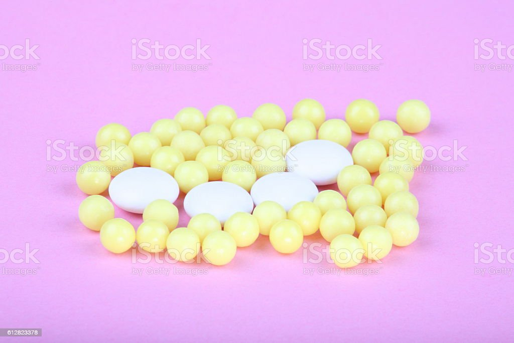 yellow vitamins on pink background stock photo