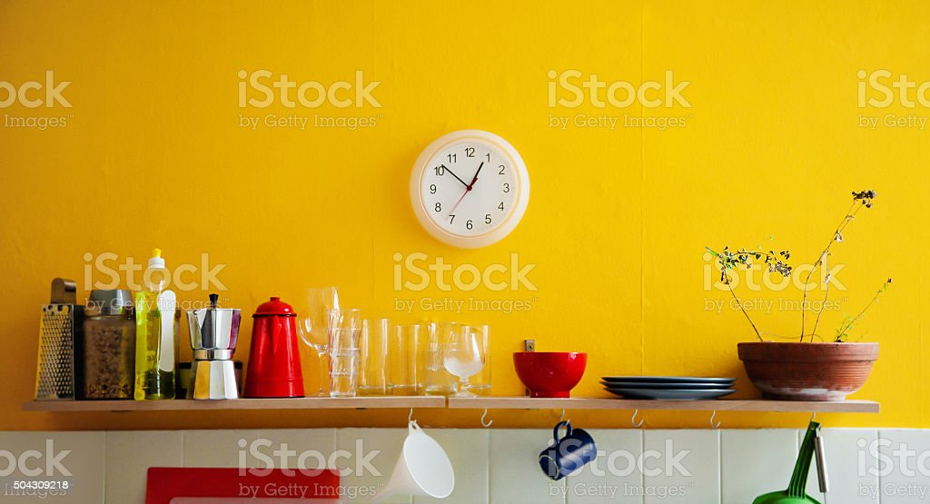Yellow wall clock in the kitchen stock photo