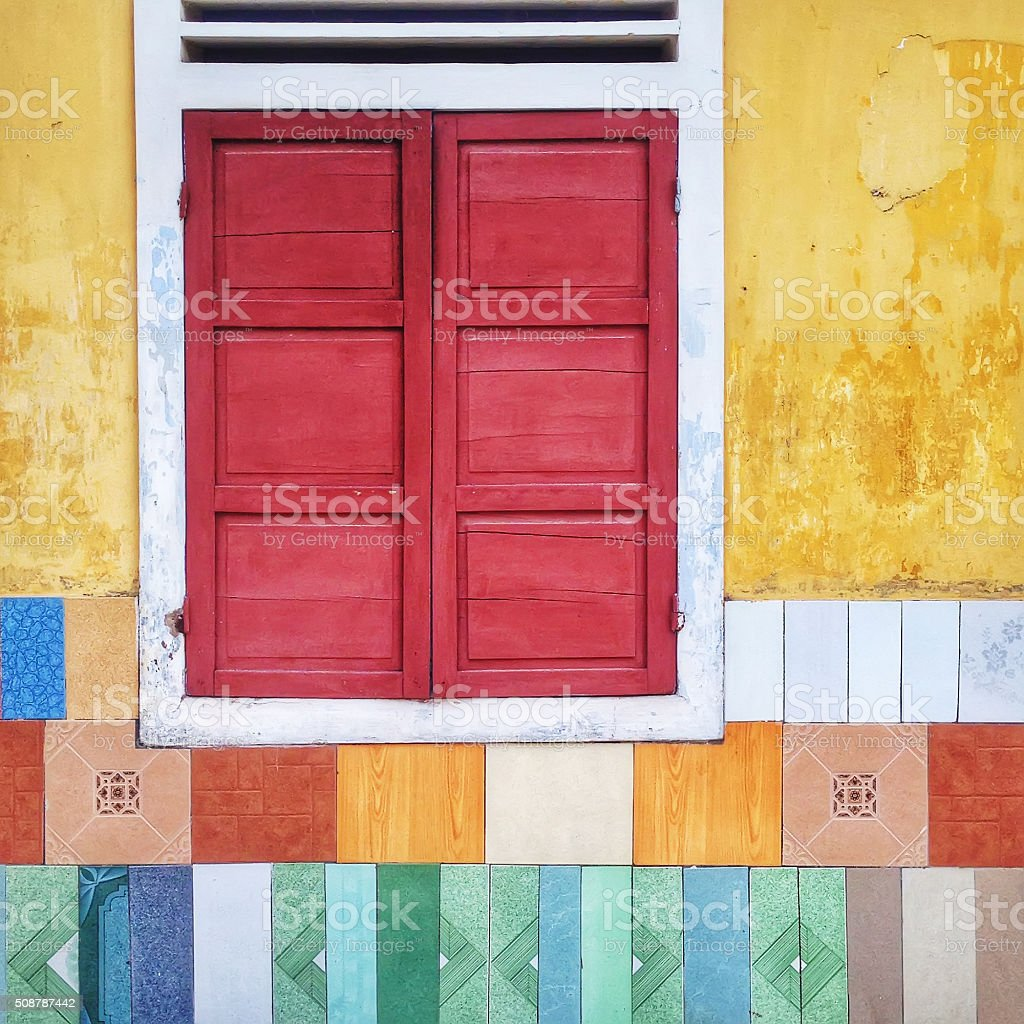 Yellow wall with red wooden window and colourful mosaic tiles stock photo