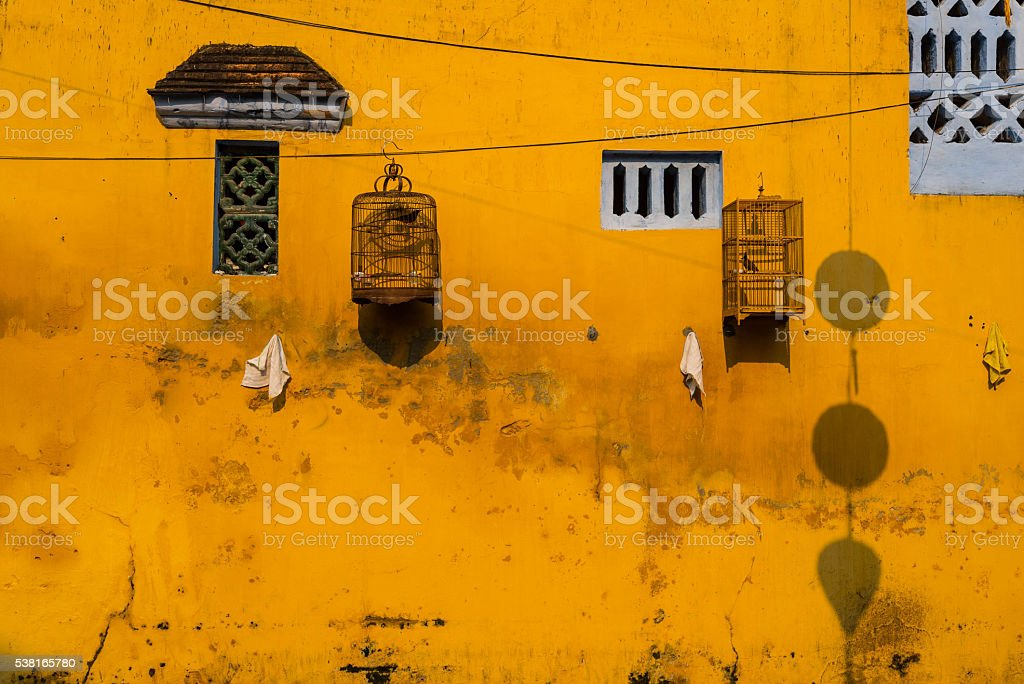 Yellow wall with small windows and bird cages stock photo