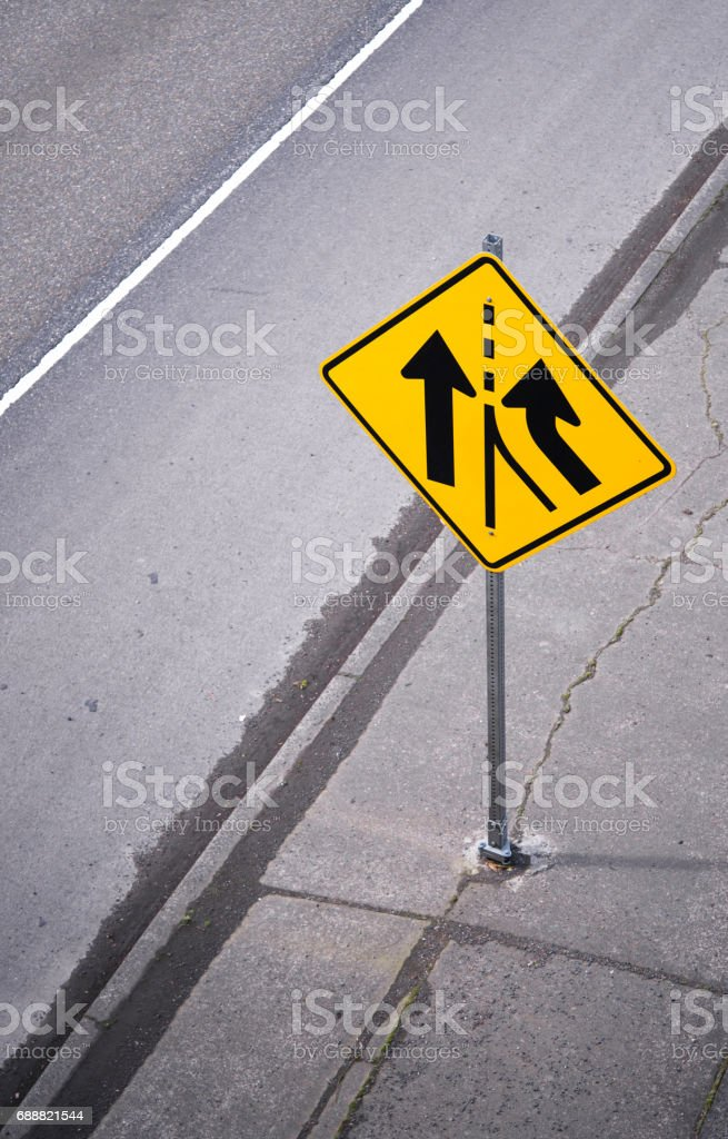 Yellow warning road sign on the road stock photo