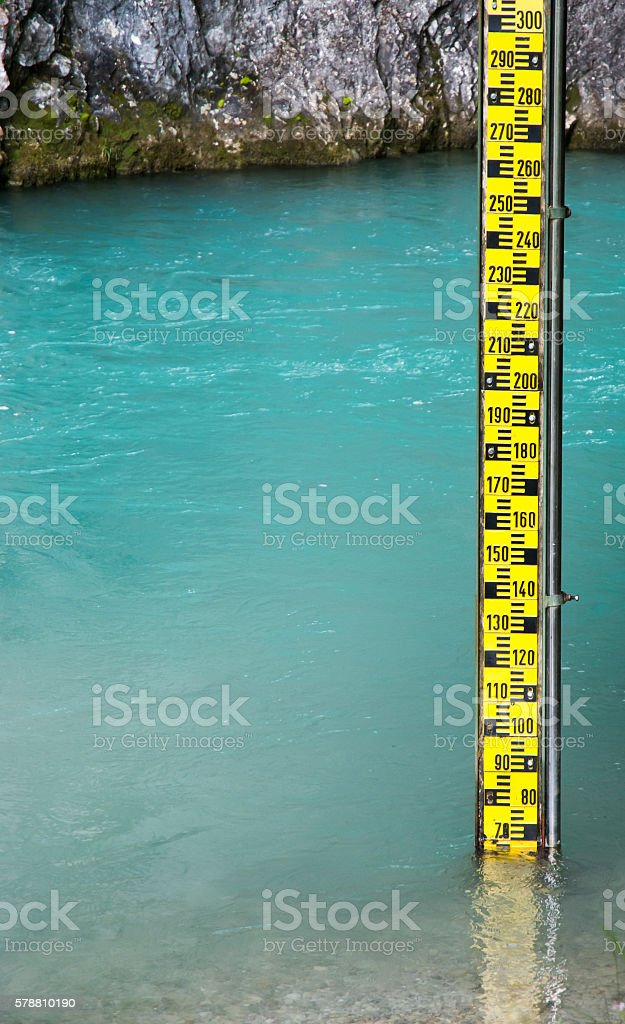 Yellow water level gauge in a river stock photo