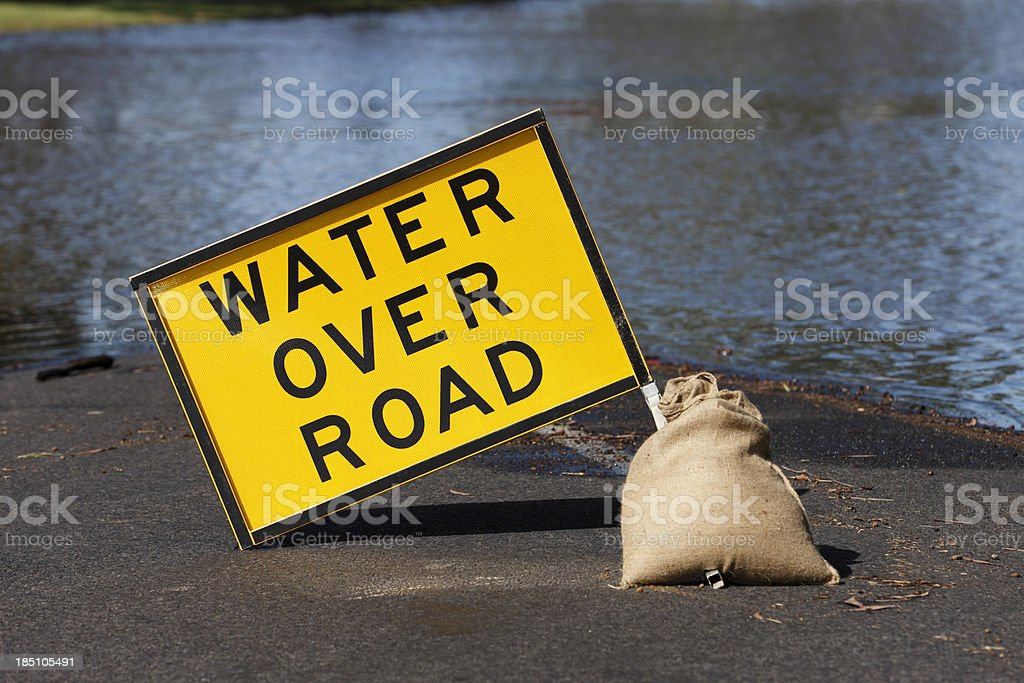 "Yellow ""Water Over Road"" hazard sign and flooded street stock photo"