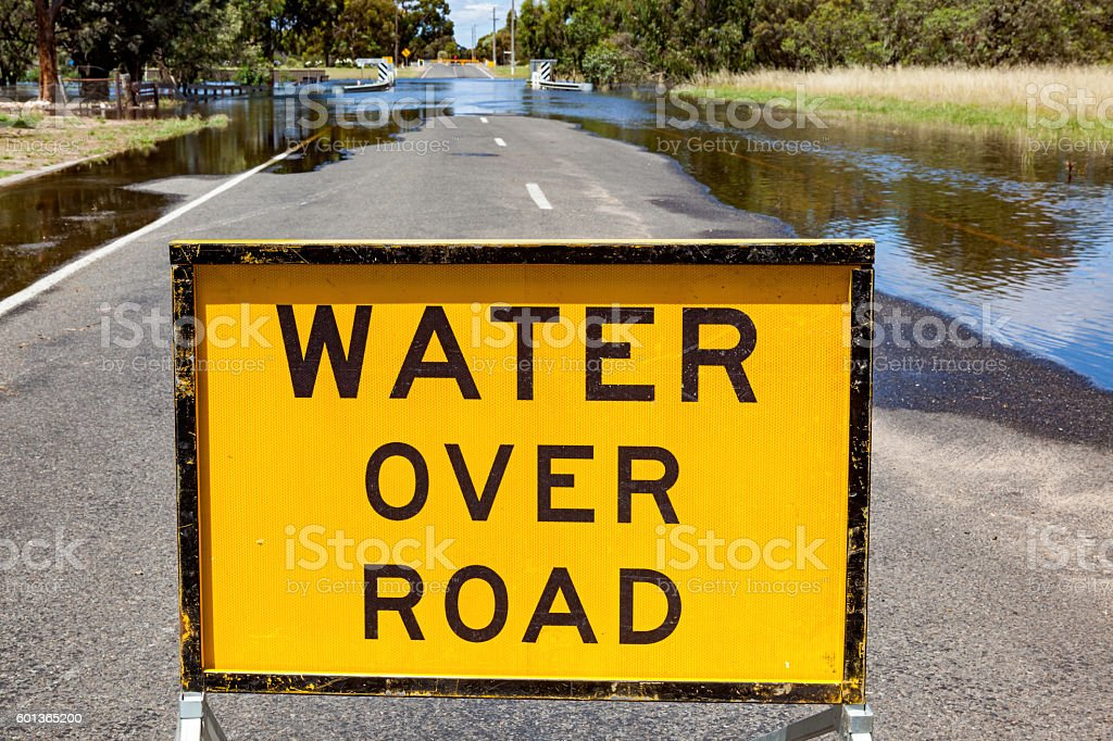 "Yellow ""Water Over Road"" sign blocks flooded road stock photo"