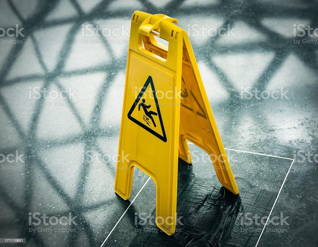 Yellow wet floor folding sign in black floor stock photo