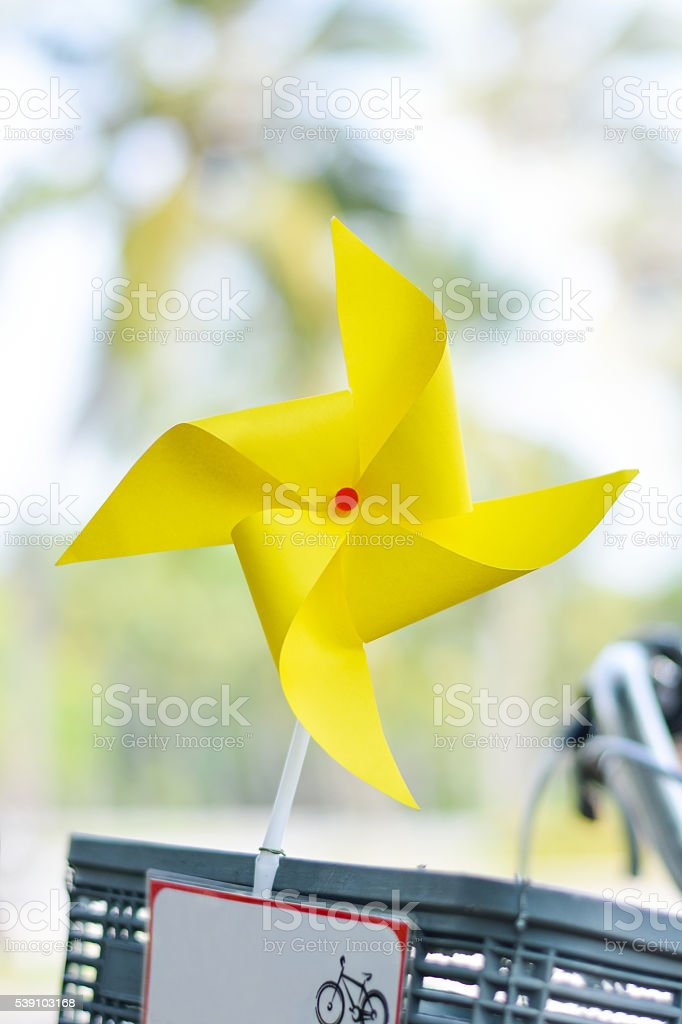 Yellow wind turbine with a bicycle stock photo