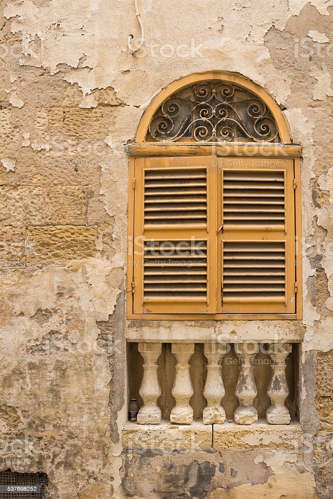 Yellow window with an arch and shutter, island Malta stock photo