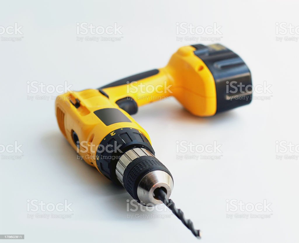 Yellow wireless power drill laying on a white backdrop stock photo