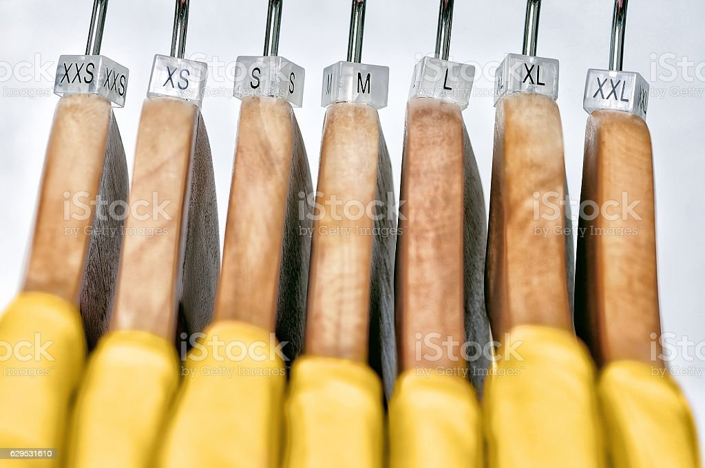 Yellow women's t-shirts of various sizes hanging on wooden hange stock photo