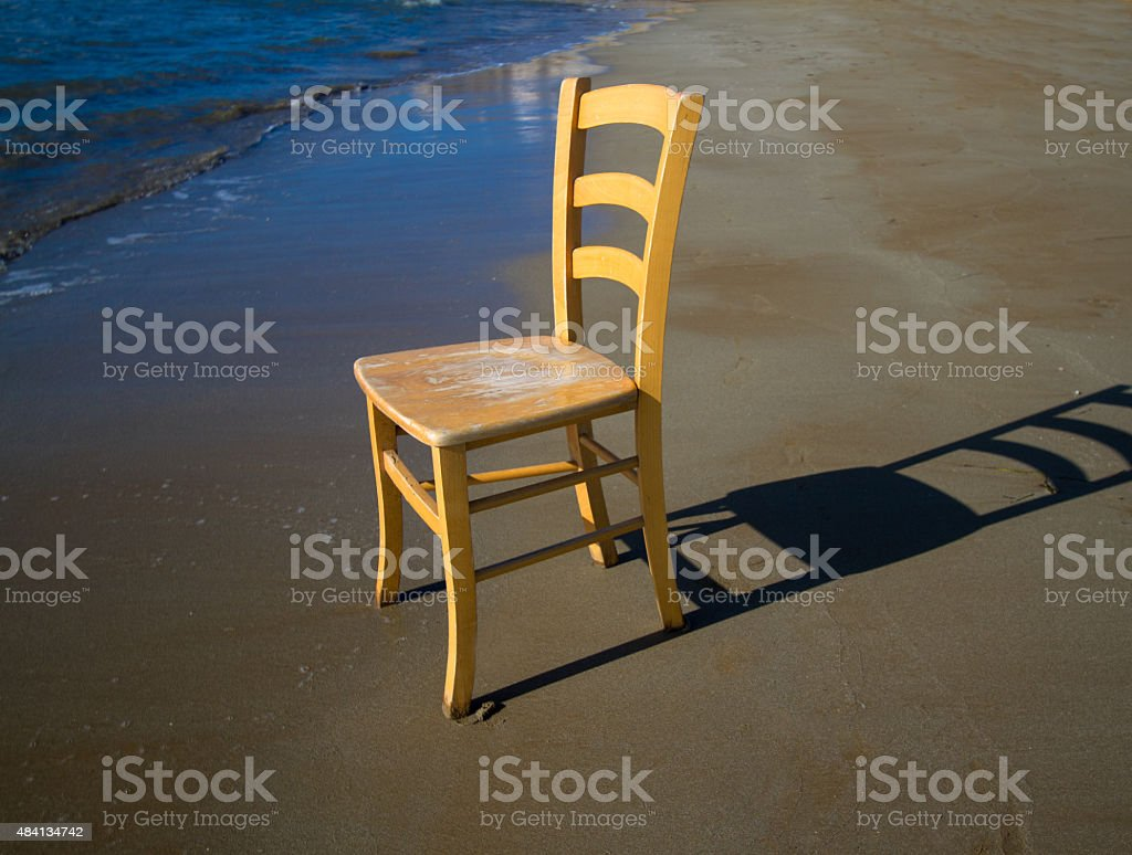Yellow Wood Chair on Sandy Beach; Early Morning stock photo