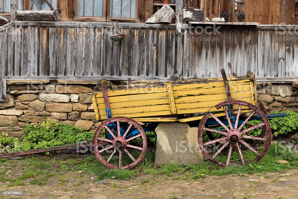 Yellow wooden waggon in front of old house in Jeravna village stock photo