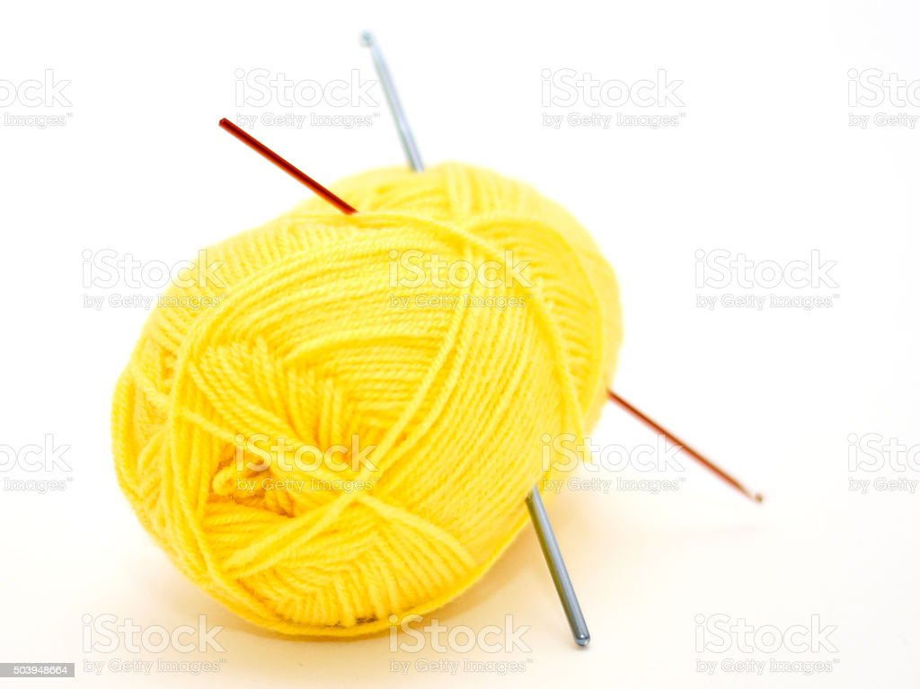 Yellow yarn ball with crochet needle stock photo