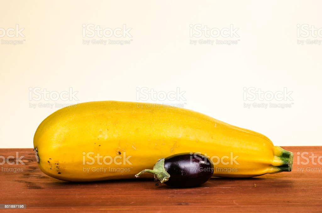 yellow zucchini with a small aubergine an a wooden underground stock photo