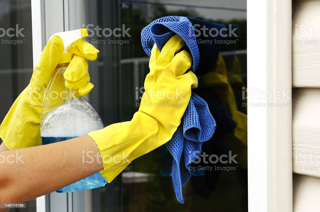 Yellow-gloved hands cleaning a window with glass cleaner royalty-free stock photo