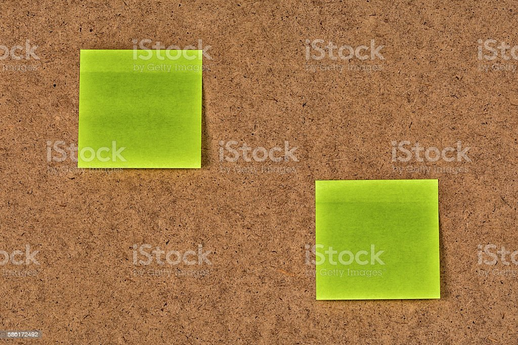 Yellow-green blank paper stickers on the old fibrous cardboard stock photo