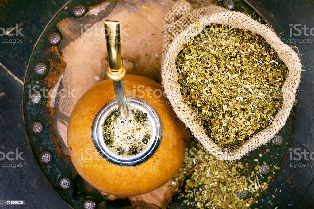 Yerba mate in a traditional gourd and dry herb stock photo