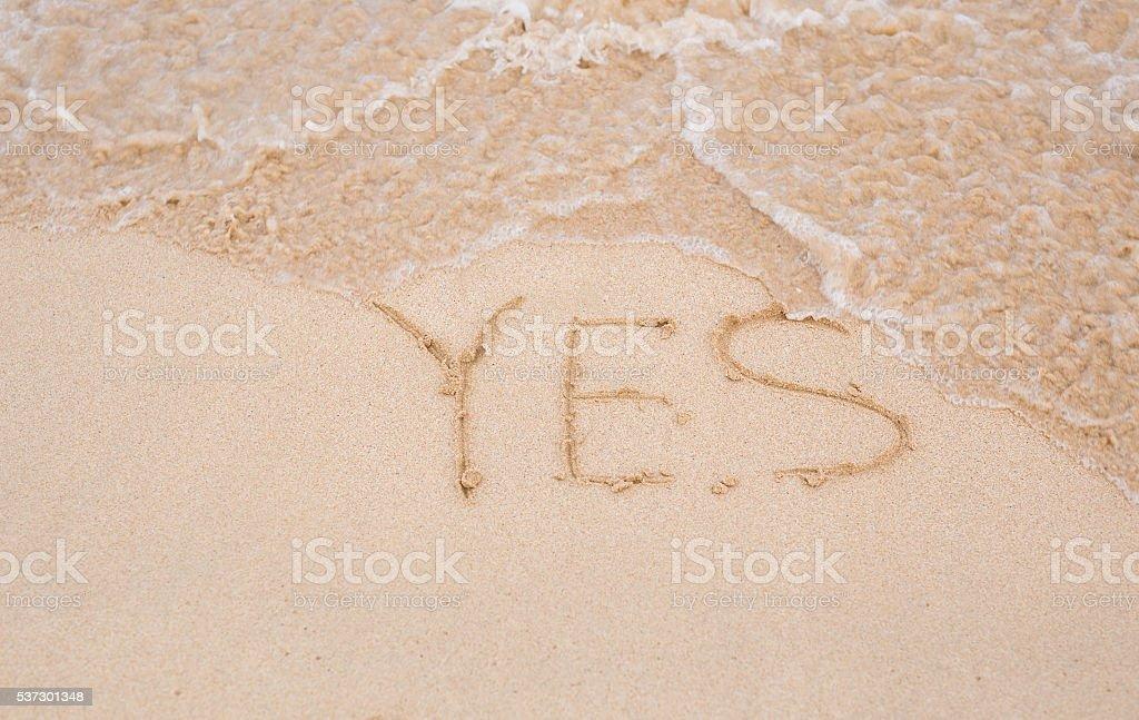 Yes - written in sand on beach texture stock photo