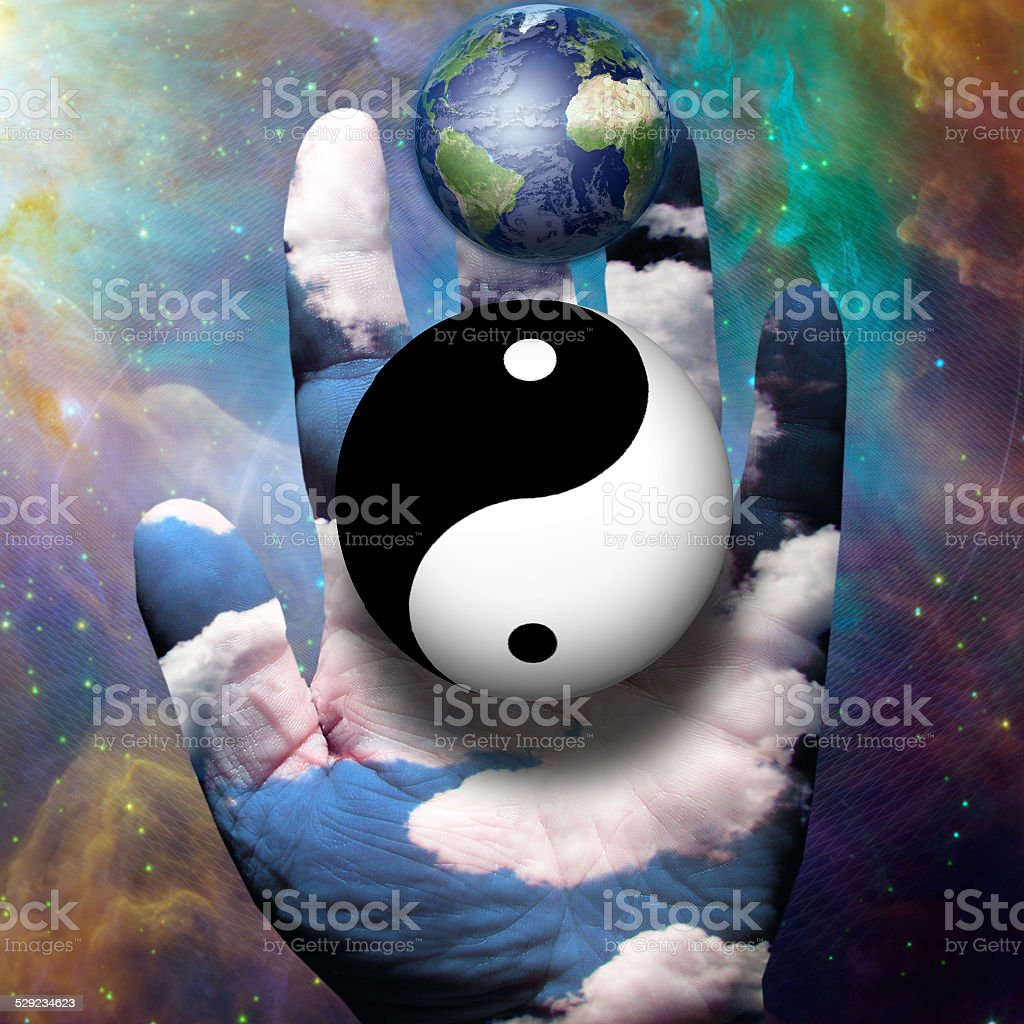 Yin Yang and Earth hover above hand stock photo