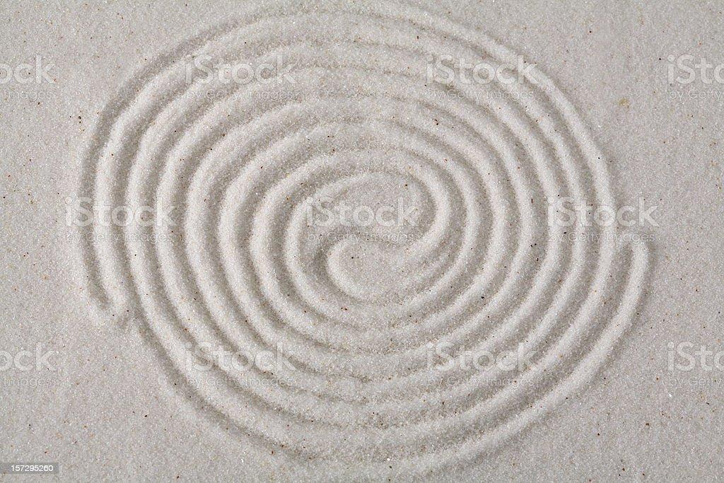 Yin-yang spirals on sand royalty-free stock photo