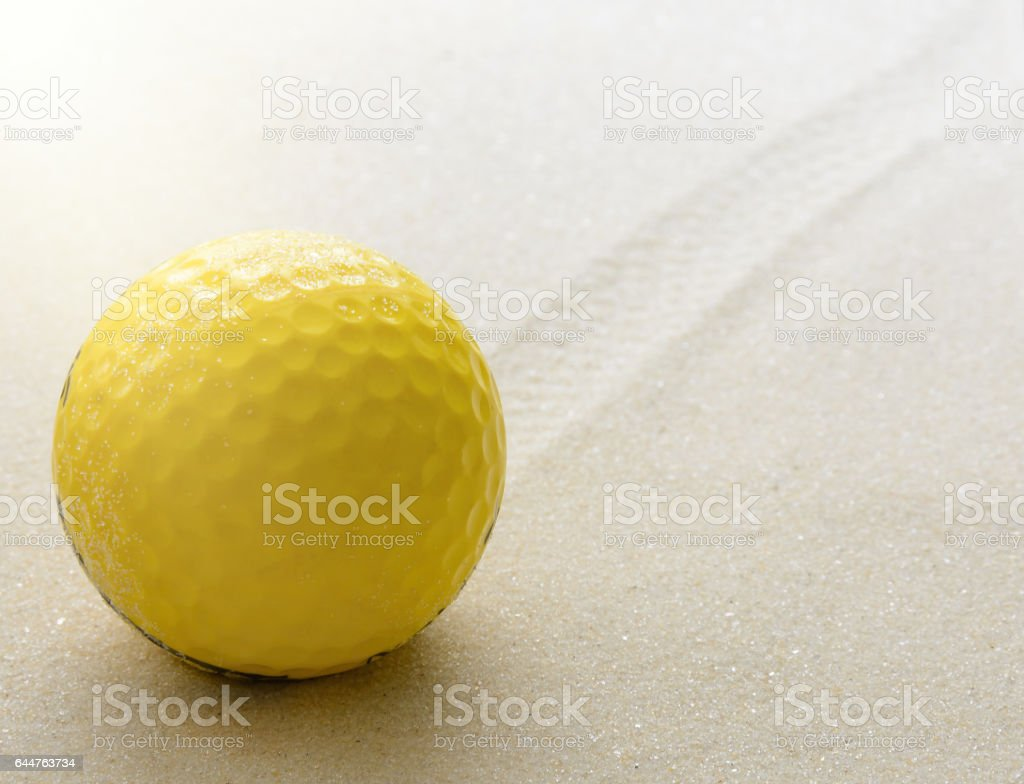 Yllow golf ball on the sand. stock photo