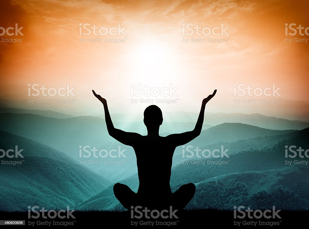 Yoga and meditation. Silhouette of man on the mountain. stock photo