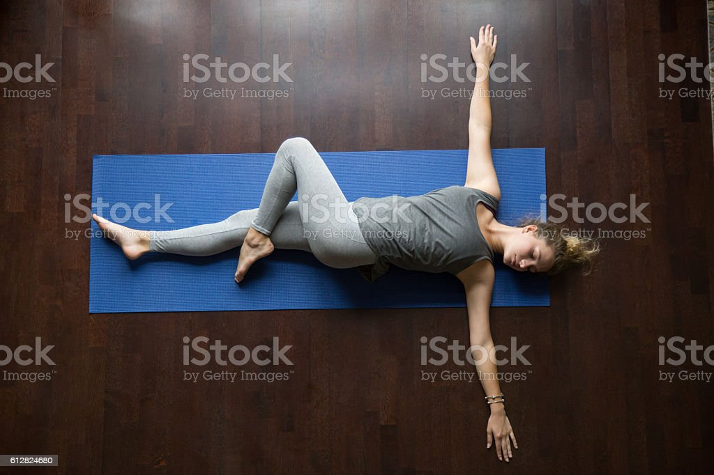 Yoga at home: Jathara Parivartanasana Pose stock photo
