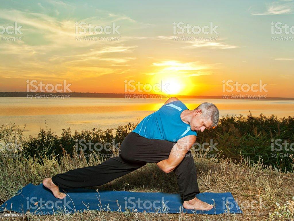 Yoga Athlete performing asana at sunset stock photo