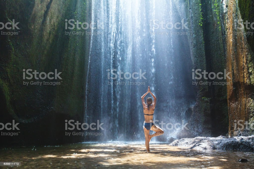 yoga, beautiful woman practices in waterfall, body and mind harmony stock photo