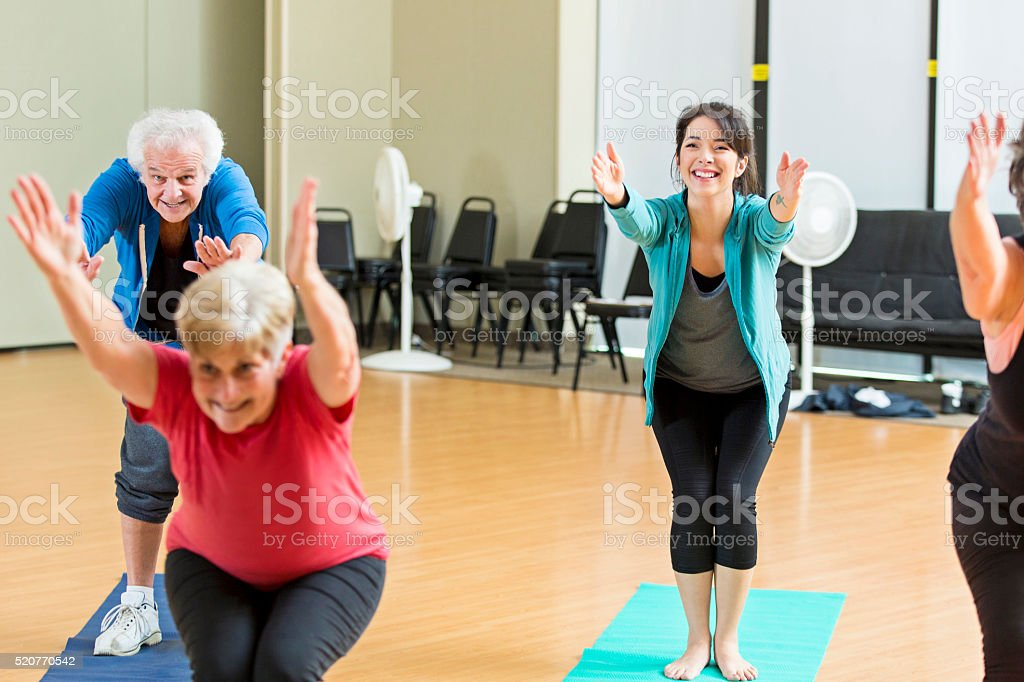 Yoga class demonstrates chair pose stock photo