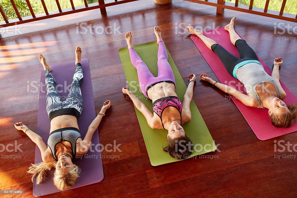 Yoga class relaxing in the Corpse pose, savasana stock photo