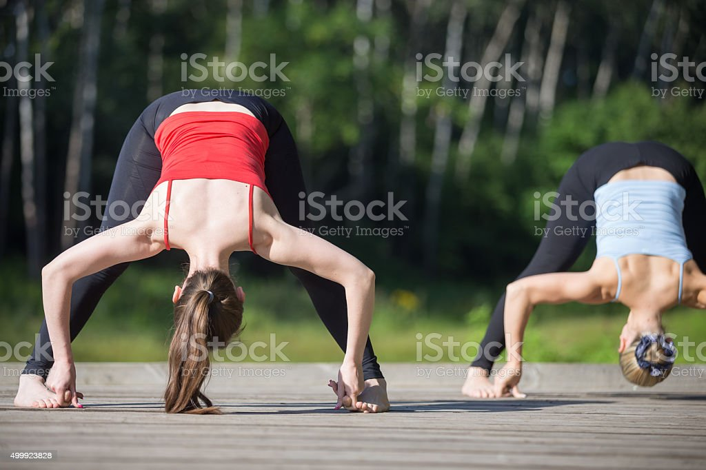 Yoga class: Straddle Forward Bend stock photo