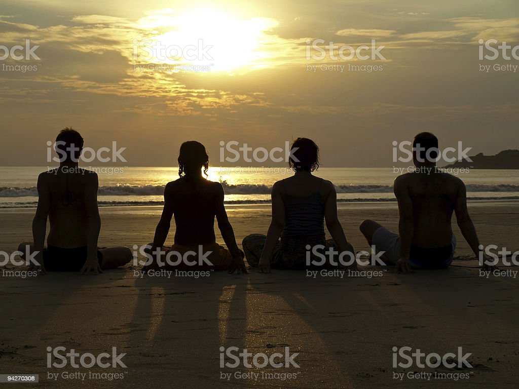 A yoga class taking place on an ocean's shore at sunset  royalty-free stock photo