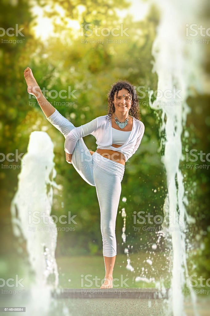 Yoga concept woman pose with water fountain stock photo
