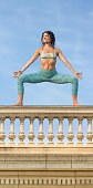 Yoga concept woman posing exercises outdoors on balustrade