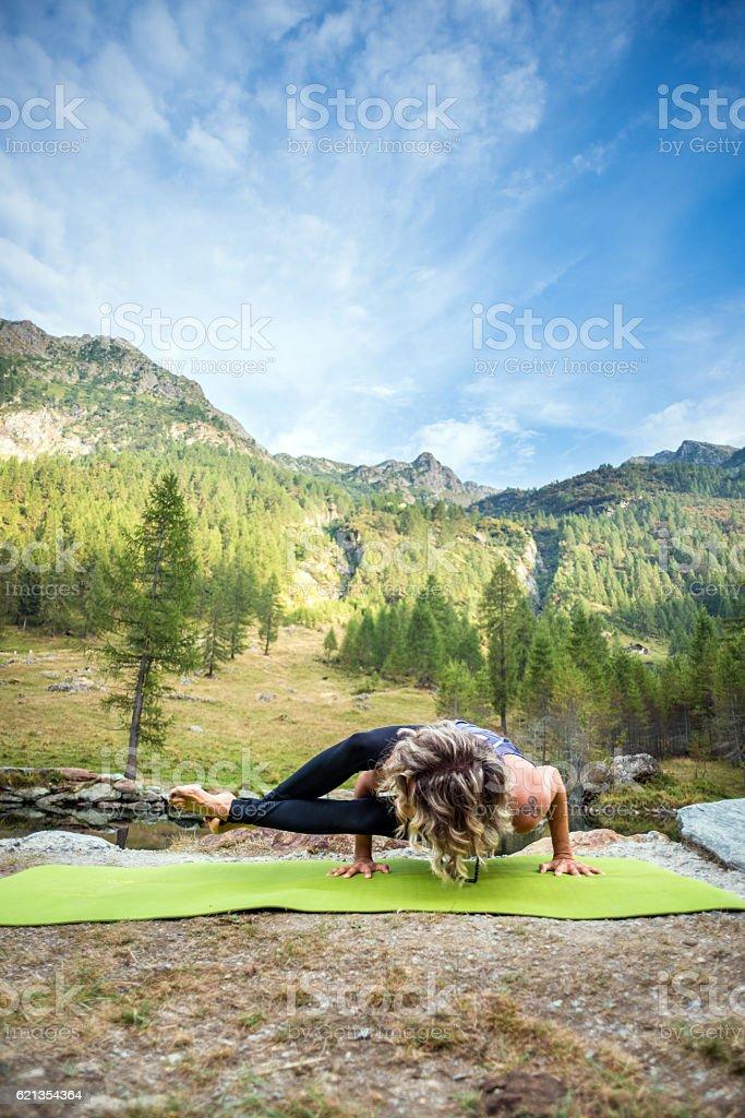 Yoga exercises in nature: Astavakrasana, Eight angle Pose stock photo