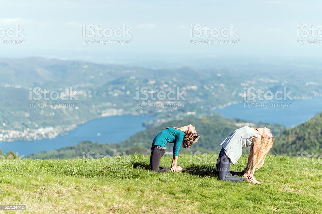 Yoga exercises in nature on mountains: camel pose stock photo