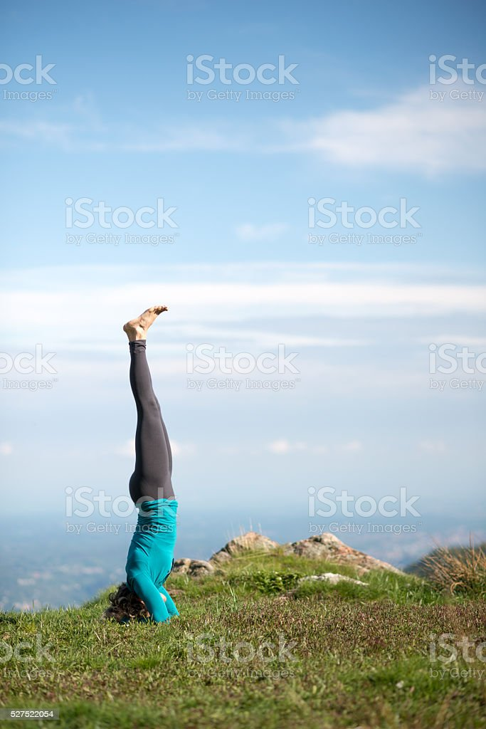 Yoga exercises in nature on mountains: headstand stock photo