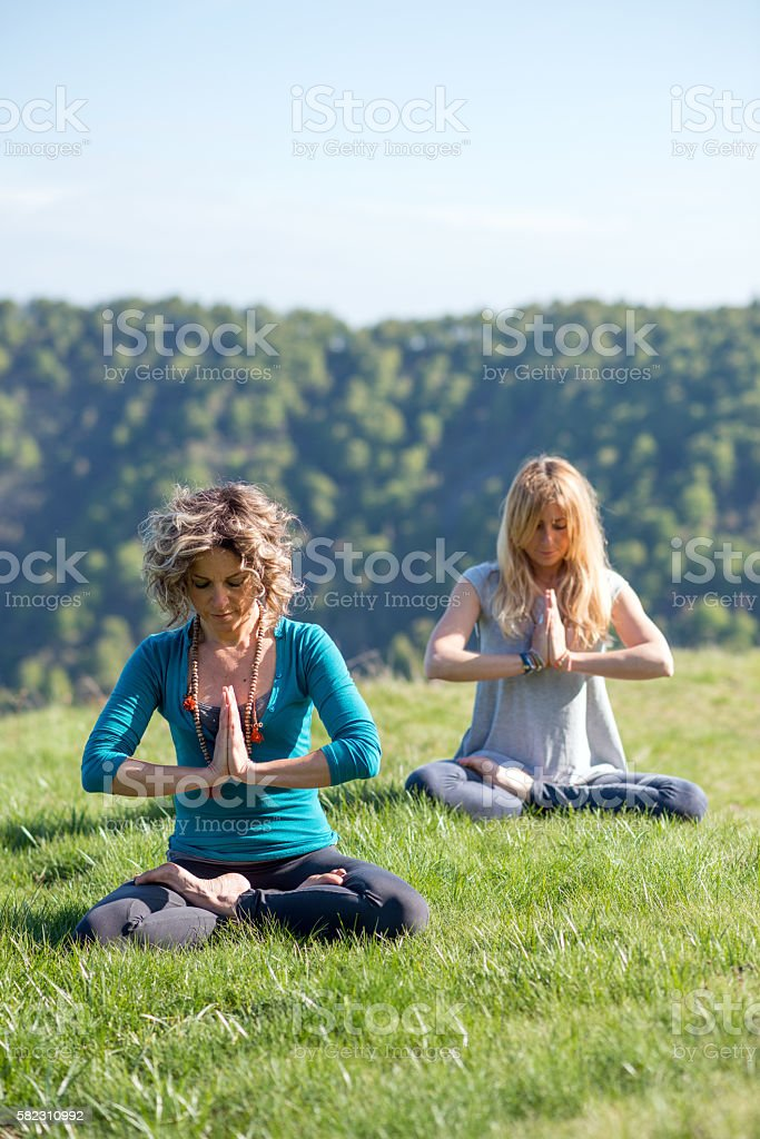 Yoga exercises in nature on mountains: Padmasana stock photo