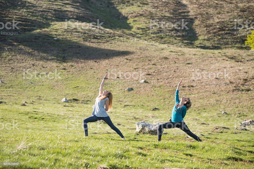 Yoga exercises in nature on mountains: reverse warrior pose stock photo