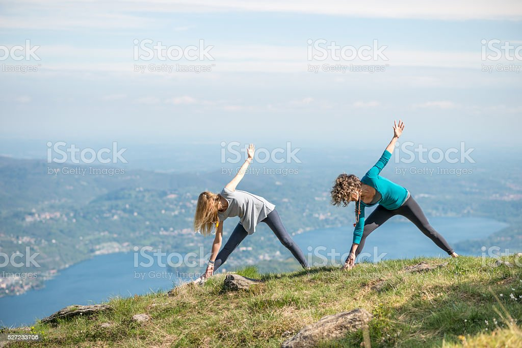 Yoga exercises in nature on mountains: triangle pose stock photo