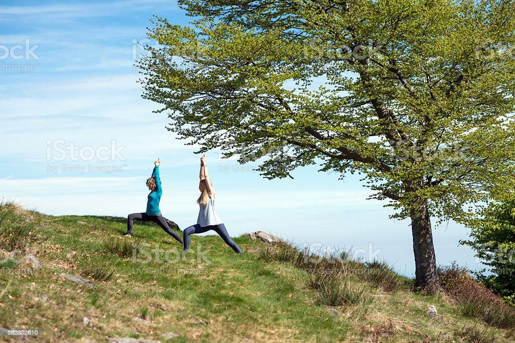 Yoga exercises in nature on mountains: Warrior 1 pose stock photo