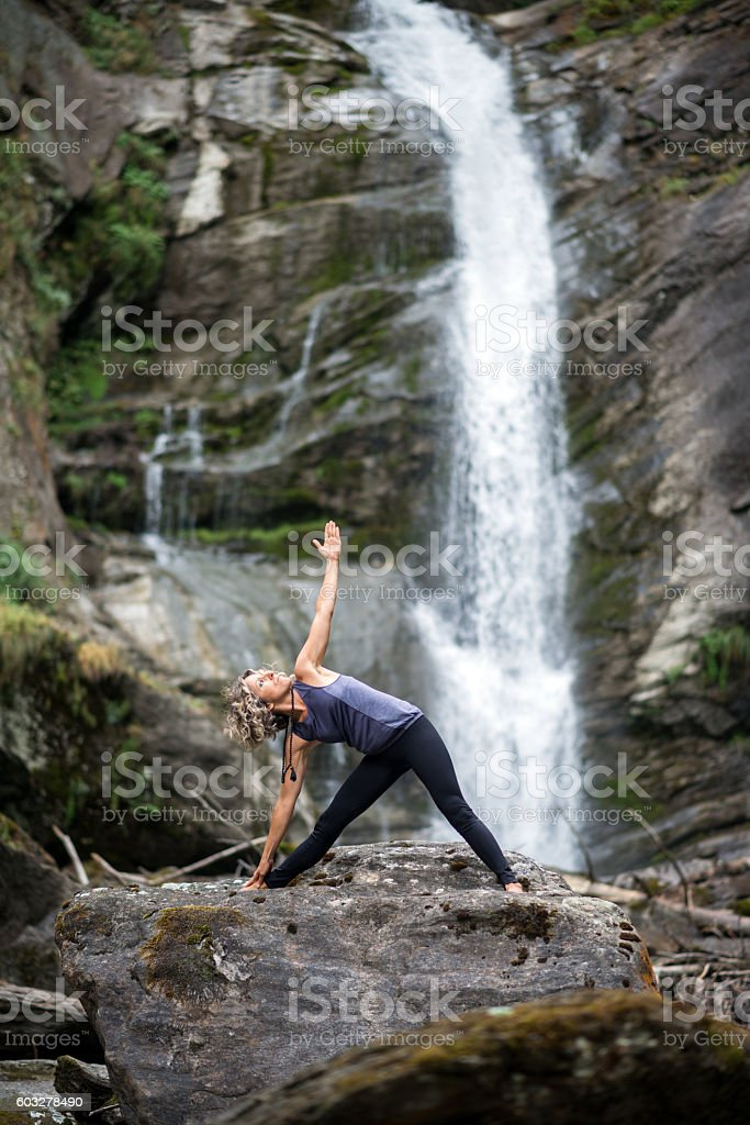 Yoga exercises in nature: Triangle pose stock photo